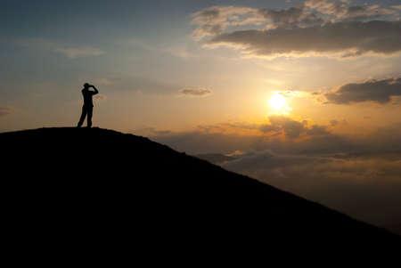 Man at the peak watching the sun Stock Photo - 6789398