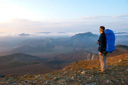 Hiker on a peak enjoys mountain landscape   photo