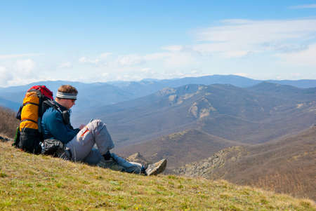 Hiker using mobile device in mountains photo