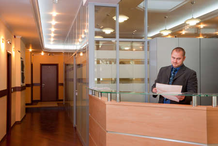 reception room: Businessman in the modern office looks at the document