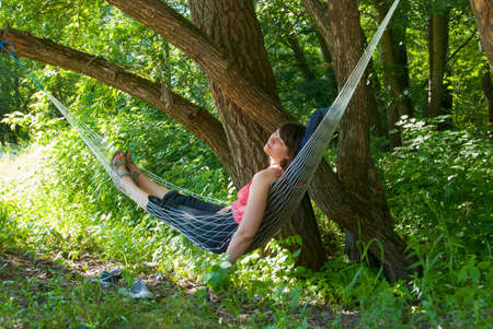 Woman relaxing in the hammock in a wood photo