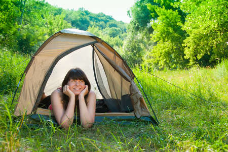 Young woman resting in a tent on the nature photo