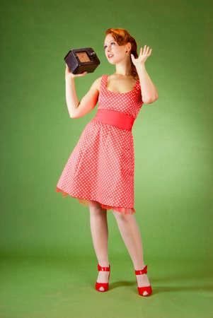 personas escuchando: Chica pin-up de estilo escuchando radio viejo  Foto de archivo