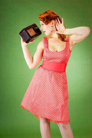 Chica pin-up de estilo escuchando radio viejo  Foto de archivo