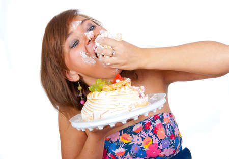 Girl eating cake with his hands, her face stained cream.  Stock Photo - 7314727
