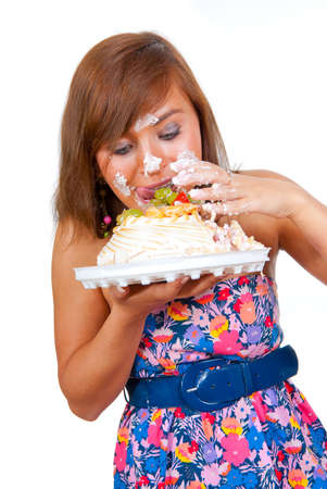 Girl eating cake with his hands, her face stained cream.  photo