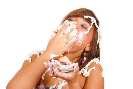 Girl eating cake with his hands, her face and head stained cream.  photo