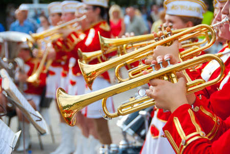 Girl Brass Band in red uniform performing photo