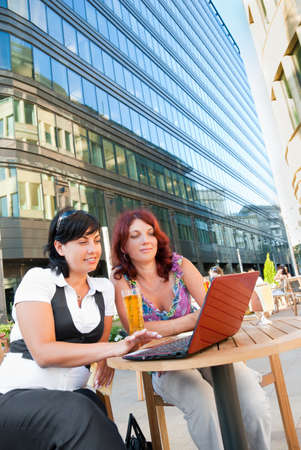 Two middle-aged women sitting in a cafe in downtown,and watching something in laptop photo