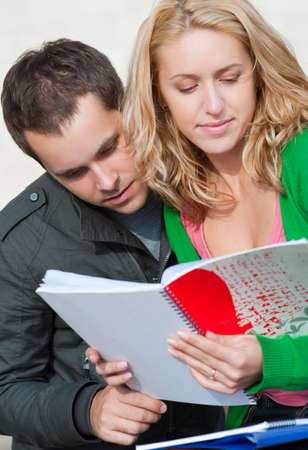 A pair of students read the notebook photo