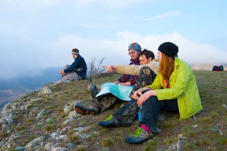 Hikers sit on the peak and exploring the map photo