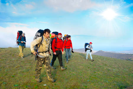 trekking: Hikers group walking in spring mountains Stock Photo
