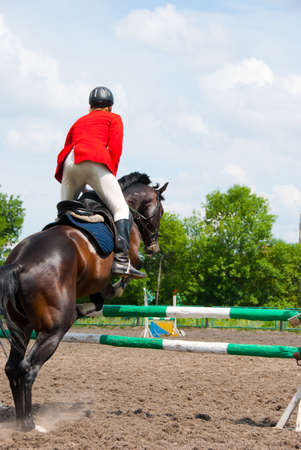Rider jumping over the barrier at the event photo