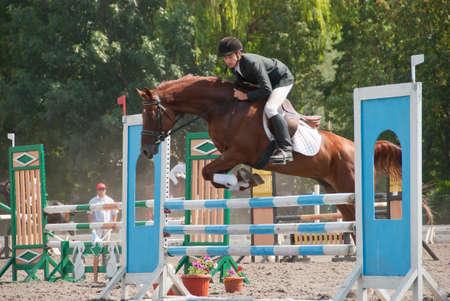 Jockey saute sur un obstacle à la compétition.  Image a un mouvement flou