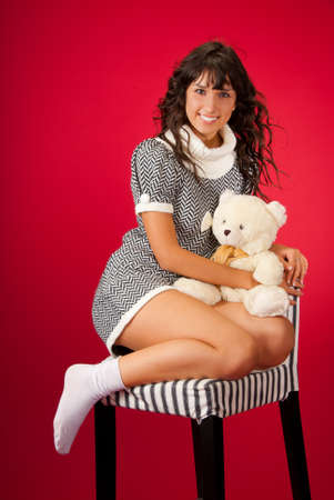 Portrait of beautiful slim young woman with Teddy over red background photo