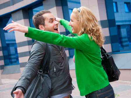 Two attractive young people met in the street and they are happy photo