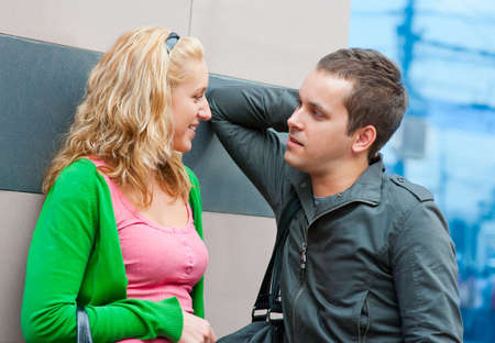 Young couple standing and talking in a city photo