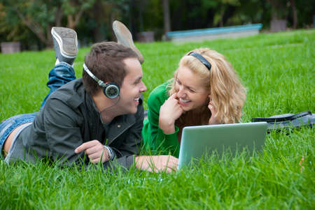 Young couple relax and listen to music from laptop on the grass in the park photo