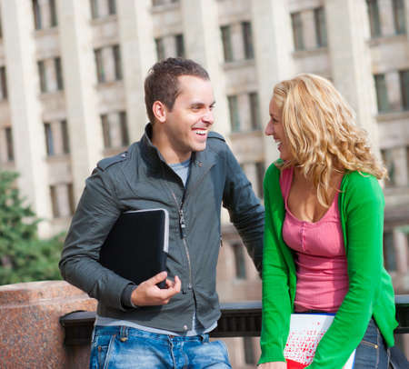 friends talking: Two attractive happy students talking at campus Stock Photo