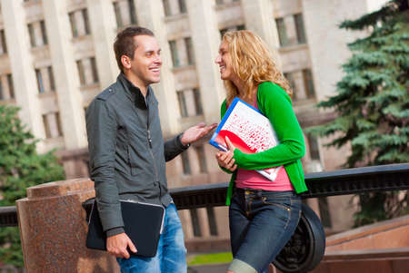 Two attractive happy students talking at campus Stock Photo - 8362300