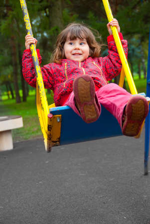 Girl swinging on a swing in the park photo