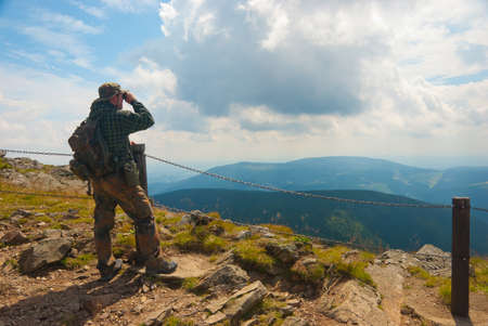 Hiker stands on a peak and enjoy the scenery through binoculars photo