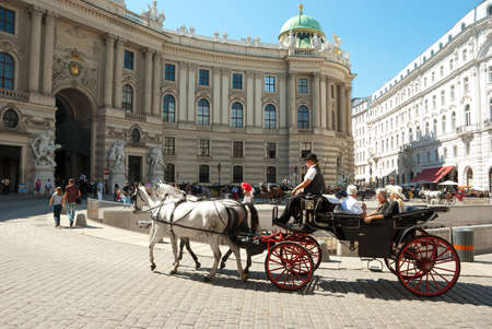 vienna: VIENNA, AUG 22 - Tourists ride through the old town on a cab, visiting the famous landmark - Hofburg Palace at August 22, 2010 in Vienna, Austria