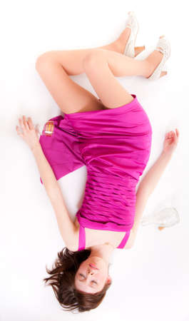 Beautiful girl in red dress sleeping with an empty glass in his hand photo