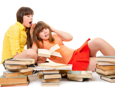 Two schoolgirls were tired of reading books and want to sleep photo