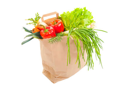 Grocery bag full of fresh vegetables isolated on white photo