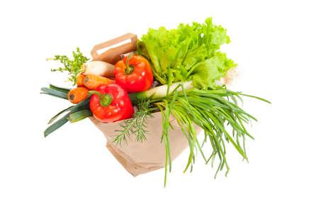 Grocery bag full of fresh vegetables isolated on white photo