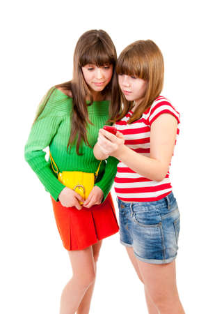 Two schoolgirls watching something in the mobile phone isolated photo