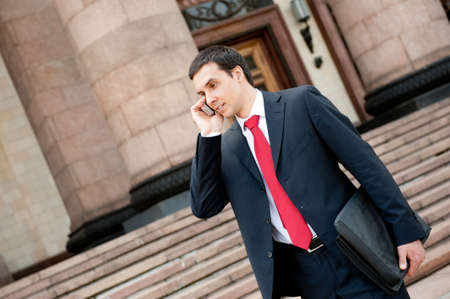 calling businessman: Businessman goes and calls on mobile in downtown Stock Photo