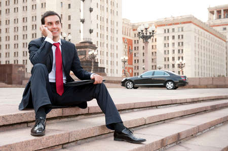 joyful businessman: Young businessman calls on mobile in downtown