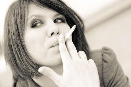 joven fumando: Retrato de mujer joven fumar cigarrillos al aire libre en tonos Foto de archivo