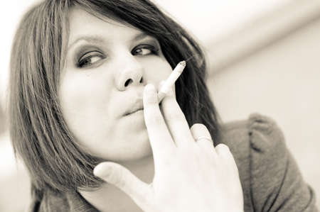 Young woman smoking cigarette outdoors toned portrait photo