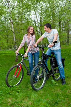 Happy young couple riding bicycles in a park photo