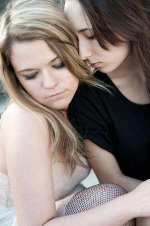 Two sad girls sorry for each other outdoors photo
