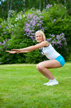 An active beautiful caucasian woman doing sit-ups in the park Stock Photo - 9756913