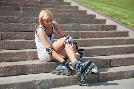 Young woman wears roller skates on the stairs photo