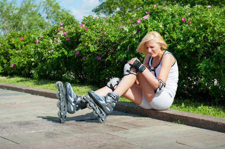 leg pain: Blonde woman has hit a knee skating on roller-skaters and it hurts Stock Photo
