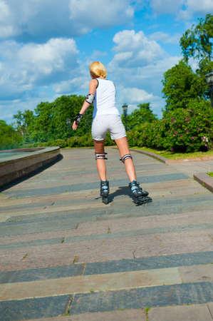 Chica rubia sobre patines paseos en el Parque Foto de archivo - 9758137