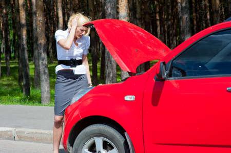 Blonde girl looks under the hood of a broken car Stock Photo - 9954951