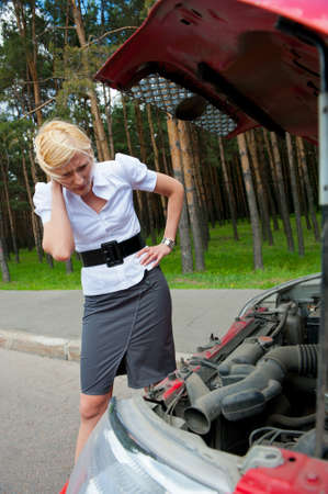 Blonde girl looks under the hood of a broken car photo