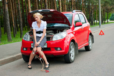 Blonde girl helplessly sitting on the hood waiting for car service Фото со стока