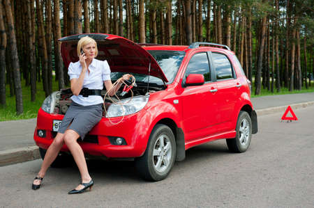 road assistance: Blonde girl sitting on the hood and calling to car service