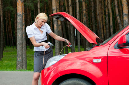 Blonde girl trying to do something with her broken car photo