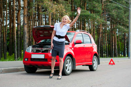 Blonde girl asks for help on the road near her broken car Stock Photo - 9954958