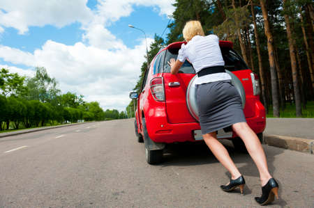 Blonde girl pushes her broken car to the car service Stockfoto