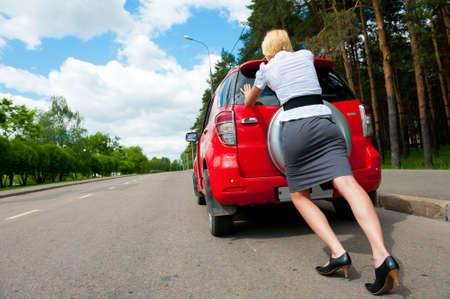 broken back: Blonde girl pushes her broken car to the car service Stock Photo